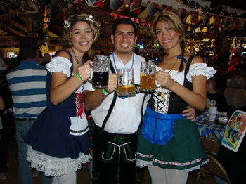 Two women and man holding up beer mugs